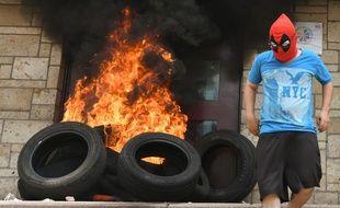 La porte de l'ambassade américaine incendiée au Honduras par des personnes masquées, en marge de manifestations, le 31 mai 2019.