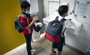 Dans une école toulousaine, deux élèves portant un masque et se lavant les mains.