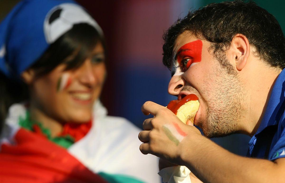 Un supporter italien dégomme un hot dog lors de la Coupe du monde 2006, en Allemagne. – PATRICK HERTZOG / AFP