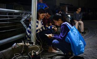 Des Vénézuéliens rechargent leur téléphone dans des magasins où il reste du courant alors qu'une nouvelle panne d'électricité plonge dans la pénurie et le noir le pays, déjà affecté par une immense panne du 7 au 14 mars 2019.