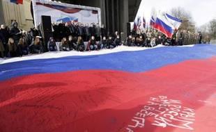 """Des manifestants déploient un drapeau russe géant avec l'inscription: """"La Crimée et la Russie, ensemble pour toujours"""", le 16 mars 2015 à Simféropol"""
