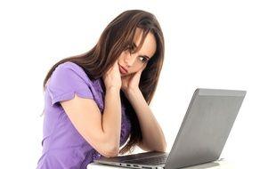 Une jeune femme regarde un ordinateur portable. Photo d'illustration.
