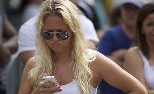 Une femme essaie son nouvel iPhone, à Miami, en 2012.
