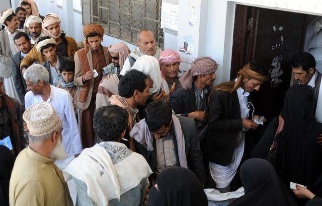 Des Yémenites font la queue pour obtenir des rations de nourriture dans un centre de Sanaa.