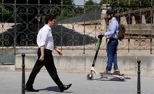 Un homme fait de la trottinette à Paris.