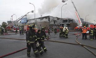 Des pompiers interviennent dans un supermarché incendié à Santiago, au Chili, le 20 octobre 2019.
