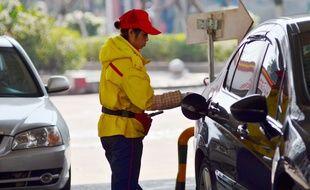 Une jeune femme qui fait son plein d'essence à Pékin