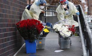 Des infirmières du service des urgences de l'hôpital Elmhurst à New York transportent des fleurs reçues en don, le 28 mars 2020.