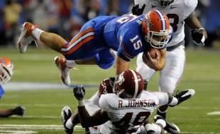 Le quarterback des Gators Tim Tebow survole les débats et ses adversaires de l'université d'Alabama, en football américain universitaire.