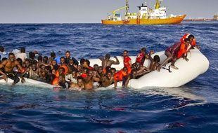 Des migrants en détresse attendent d'être secourus par l'Aquarius, le bâteau d'SOS Méditerranée (au fond).