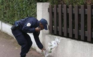 Un policier dépose une fleur à côté de la maison des policiers tués à Magnanville