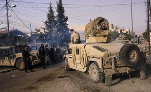 Un soldat de l'armée irakienne, assis sur le toit de son Humvee, le 10 janvier 2017 dans l'est de Mossoul.