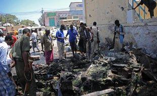 Des passants observent les restes de la voiture piégé qui a explosé le 15 avril 2015 devant le ministère de l'Education somalien à Mogadiscio