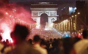 La foule célèbre la qualification de l'équipe de France de football en finale de la Coupe du monde sur l'avenue des Champs-Elysées, à Paris, le 10 juillet 2018.