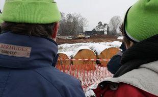 Avec leurs bonnets verts sur la tête, deux opposants au projet autoroutier controversé du Grand contournement ouest de Strasbourg assistent à des travaux de terrassement à Vendenheim, à l'emplacement du futur échangeur nord.