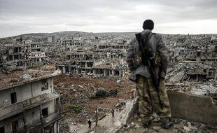 Un soldat kurde fait face à la ville détruite de Kobané, en Syrie.