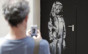 L'oeuvre au pochoir, attribuée à Banksy, représente un personnage en recueillement sur l'une des portes arrières du Bataclan, le 25 juin 2018.