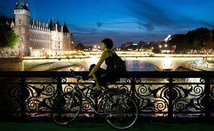 La tombée de la nuit, moment idéal pour une balade à vélo sur la Seine à Paris. Le 19 juillet 2010.