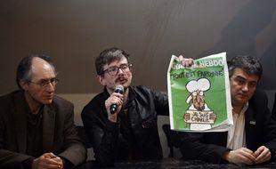 Luz, entouré de Gérard Biard et Patrick Pelloux, montre la Une de