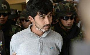 Un suspect dans l'enquête sur l'attentat de Bangkok, Yusufu Mieraili (c), escorté par des policiers, le 7 septembre 2015 à Bangkok