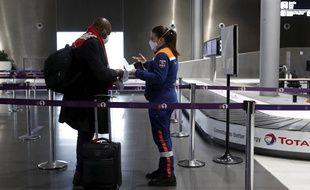 Une membre de la protection civile face à un voyageur à l'aéroport de Roissy. (illustration)