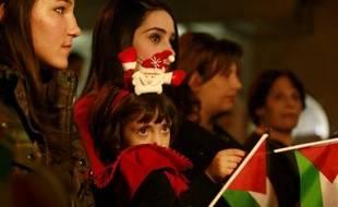 Une famille chrétienne palestinienne assiste à un office avant Noël à l'église orthodoxe de Gaza le 22 décembre 2014
