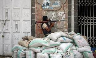 Un membre des milices pro-gouvernementales yéménites en position de combat le 24 avril 2015 dans une rue de la ville de Taëz, théâtre d'affrontements avec les rebelles chiites Houthis