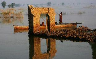 Des victimes des inondations passent en bateau parmi les maisons détruites du village de Chandan Mori Johi, Pakistan, le 30 septembre 2010.