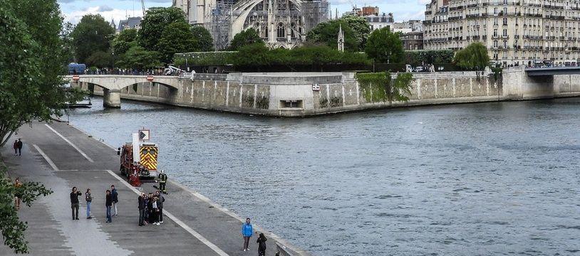 Les pompiers s'entraînent en contrebas de Notre-Dame, tandis que les ouvriers alpinistes installent des bâches pour protéger la cathédrale.