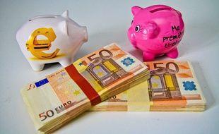 Tirelires et liasses de billets de 50 euros.