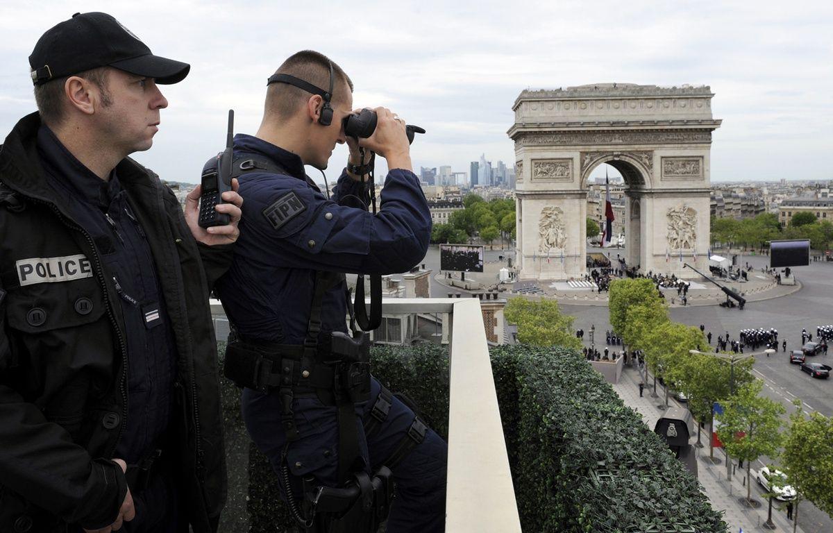 Des policiers observent les passants autour de l'Arc de Triomphe à Paris. – BERTRAND GUAY / AFP