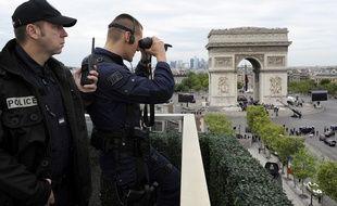 Des policiers observent les passants autour de l'Arc de Triomphe à Paris.