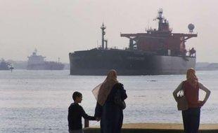Des Egyptiens regardent un tanker transiter par le canal de Suez en 2008.