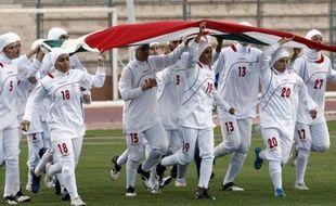 Les joueuses de l'équipe d'Iran de football courent avec leur drapeau  national à Amman, avant un match de qualifications aux JO-2012 contre  la Jordanie, qui n'a pas été disputé en raison de l'interdiction du  voile islamique, le 3 juin 2011.