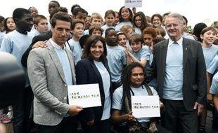 La maire de Paris Anne Hidalgo et Bernard (g) Lapasset, futur président du comité de candidature, entouré d'athlètes pour le lancement officiel de la candidature Paris-2014, le 23 juin 2015 à Paris