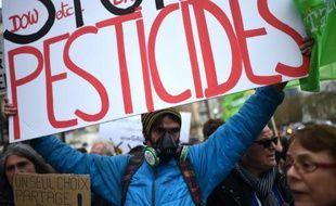 """Un manifestant tenant une pancarte sur laquelle il est écrit """"Stop Pesticides"""" le 26 mars 2016 à Paris"""