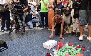 Une femme pose une bougie en mémoire des victimes des attentats de Catalogne, le 18 août 2017 à Barcelone. AFP PHOTO / JAVIER SORIANO