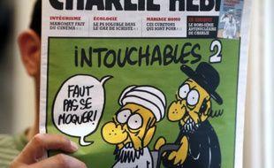 """Un homme lit le 19 septembre 2012 le numéro de Charlie Hebdo paru ce jour-là, montrant un juif et un musulman sous le titre """"Intouchables 2"""""""