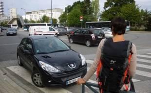 Une femme attend son covoiturage au parking La Poterie à Rennes.