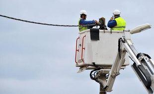 Des employés d'ERDF effectuent une réparation à Charron, en Charente-Maritime, après le passage de la tempête Xynthia le 3 mars 2010.