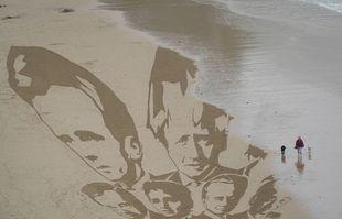 Une femme promène ses chiens alors que la marée montante commence à éloigner les têtes des dirigeants du G7 dessinés dans le sable par des militants sur la plage de Newquay, Cornwall, en Angleterre, le 10 juin 2021.