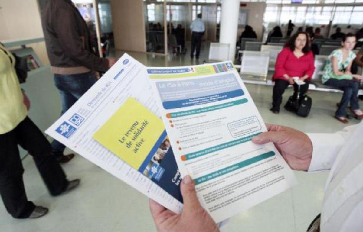 Une personne présente les brochures d'information sur le RSA mises à la disposition des usagers dans un centre de la CAF à Paris le 4 juin 2009 – Francois Guillot AFP