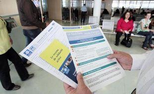 Une personne présente les brochures d'information sur le RSA mises à la disposition des usagers dans un centre de la CAF à Paris le 4 juin 2009
