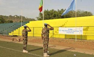 Des casques bleus de la Mission des Nations unies au Mali, la Minusma, saluent les drapeaux malien et onusien le 29 mai 2015 à Bamako