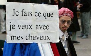 Farid Benyettou assis près d'une pancarte lors d'une manifestation en 2004.