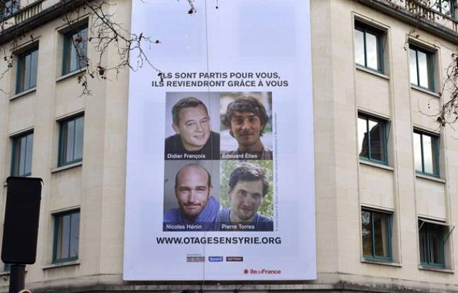Mise en place de l'affiche en soutient aux otages francais en Syrie à Paris le 6 janvier 2014