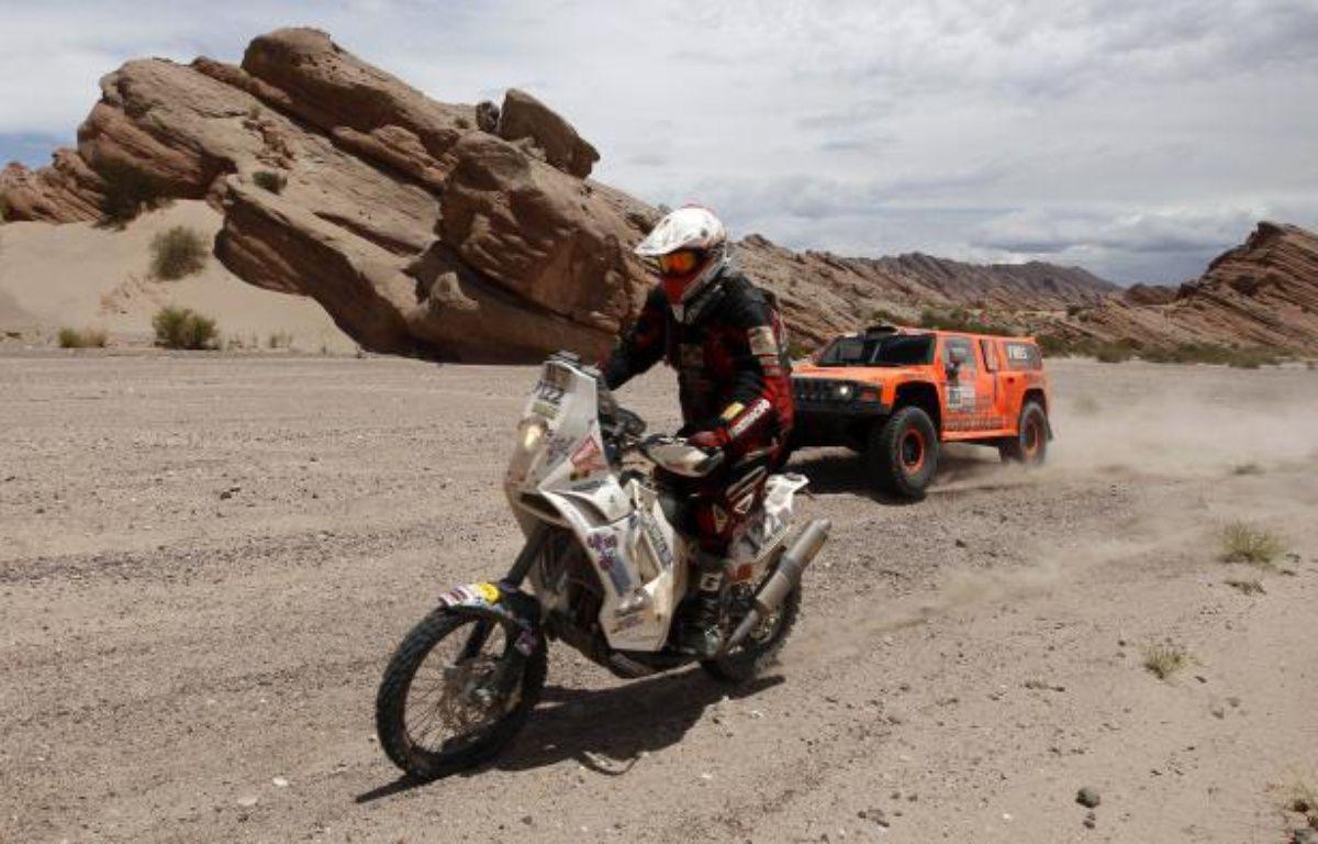 Le pilote Américain Robby Gordon (en voiture) lors du dépassement du motard Eric Palante sur le Dakar, le 4 janvier 2012 entre san Juan et Chilecito, en Argentine. – J.Naegelen/REUTERS