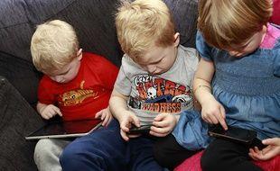 Trois enfants consultent leurs tablette et smartphone.