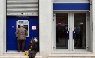Une femme demande de l'argent devant le distributeur de billets d'une banque, le 6 avril 2015 à Athènes