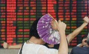 Une investisseuse tenant un éventail surveille les évolutions des actions sur le marché boursier de Shanghai le 26 août 2015